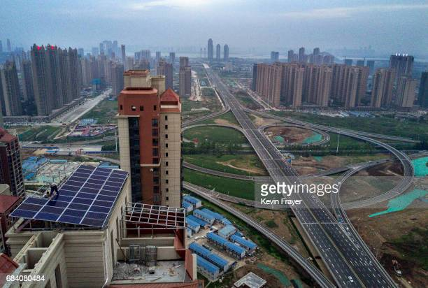 Chinese workers from Wuhan Guangsheng Photovoltaic Company works on a solar panel project on the roof of a 47 story building in a new development on...