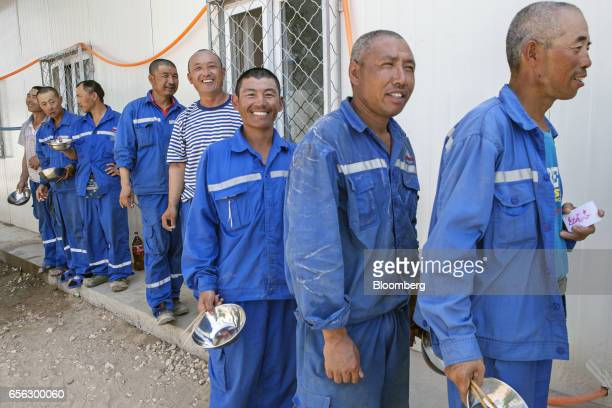 Chinese workers line up to receive their meals during a break at the Sindh Engro Coal Mining Co site in the Thar desert Pakistan on Thursday March 9...