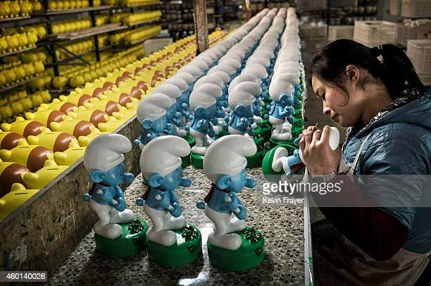 Chinese workers paint unfinished licensed ceramic 'Smurfs' at the Shunmei Group ceramics factory during a tour on December 7 2014 in Dehua Fujian...