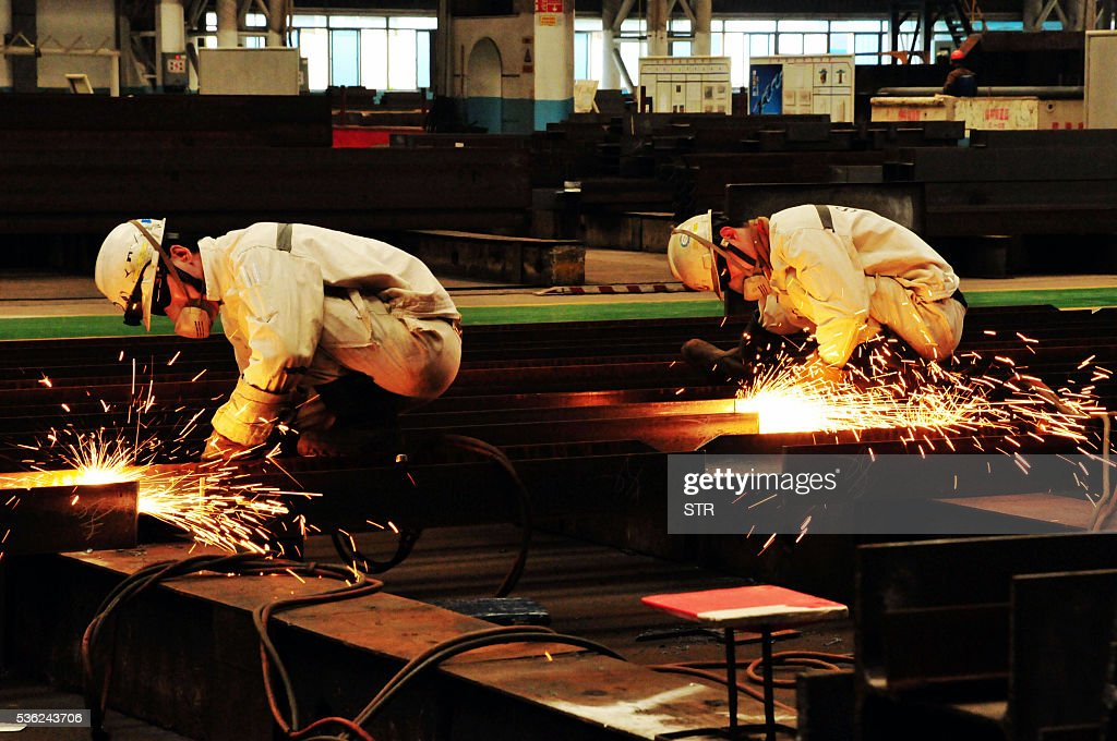 Chinese workers polish steel at an offshore oil engineering platform in Qingdao, east China's Shandong province on June 1, 2016. Activity in Chinese factories expanded for the third straight month in May, official data showed, a further sign of stabilisation in the world's second largest economy. / AFP / STR / China OUT
