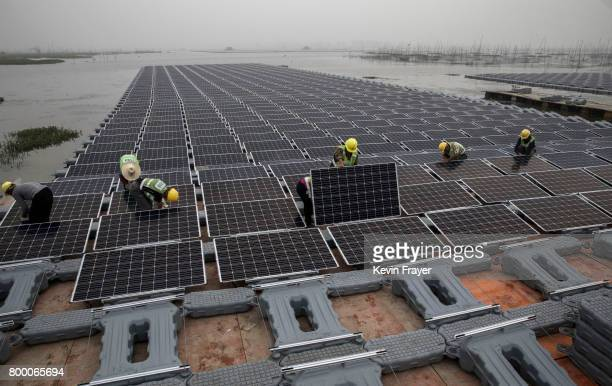 Chinese workers prepare panels that are part of a large floating solar farm project under construction by the Sungrow Power Supply Company on a lake...