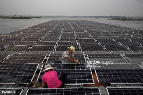 Chinese workers prepare panels that will be part of a large floating solar farm project under construction by the Sungrow Power Supply Company on a...