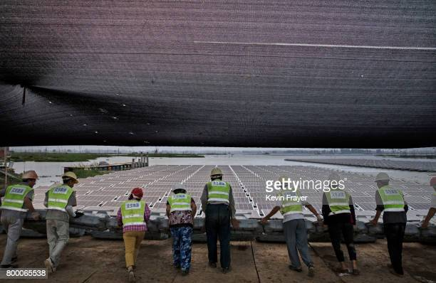 Chinese workers push a section of panels into the water that are part of a large floating solar farm project under construction by the Sungrow Power...