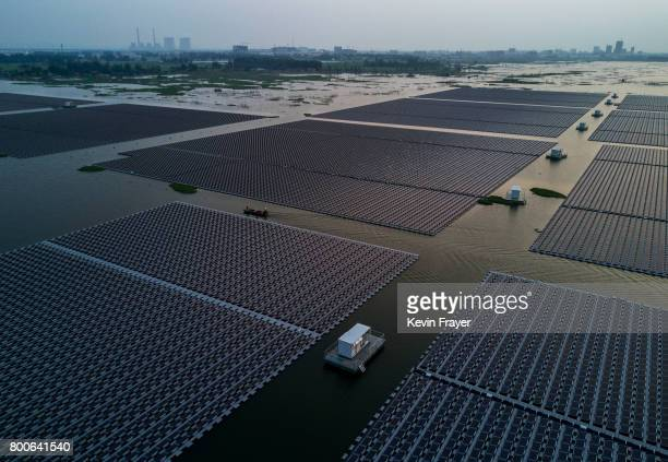 Chinese workers ride in a boat through a large floating solar farm project under construction by the Sungrow Power Supply Company on a lake caused by...