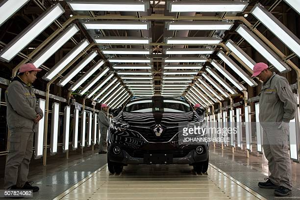 TOPSHOT Chinese workers stand next to a Kadjar car at the production line of France's Renault and China's Dongfeng Group factory in Wuhan Hubei...