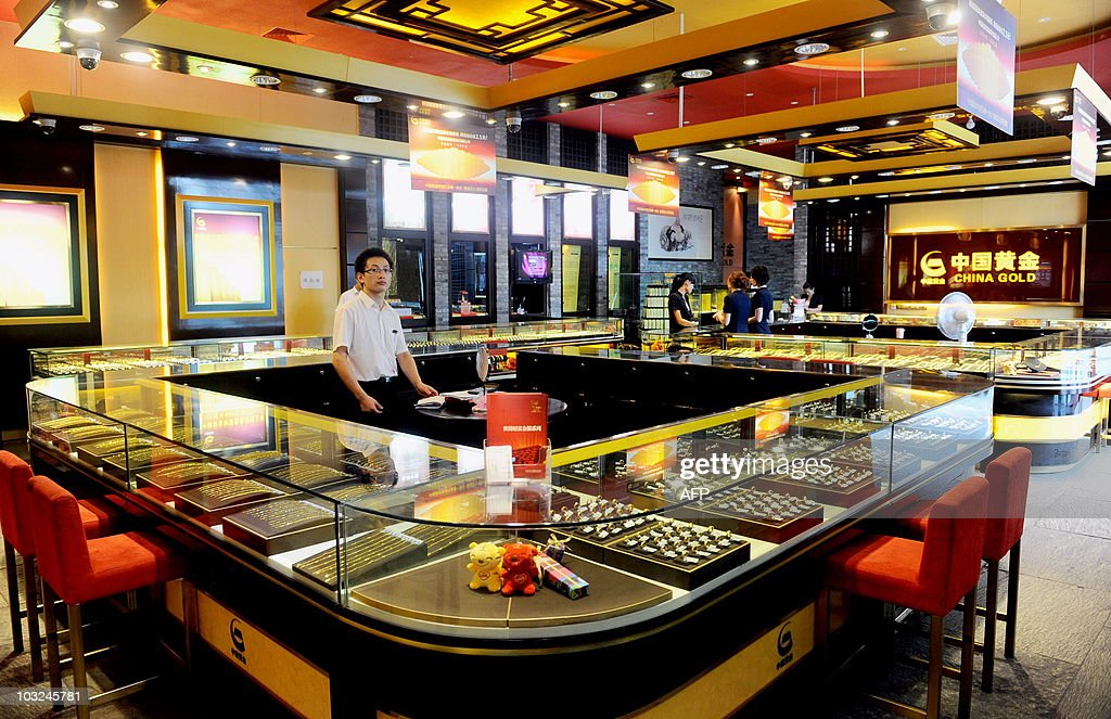 Chinese workers wait for customers at a gold shop in Beijing on August 4 2010 China has moved to further free up the nation's gold market by allowing...
