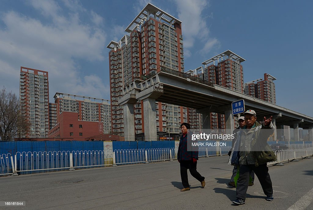 Chinese workers walk past a new property development in Beijing on April 1, 2013. Chinese home prices picked up in March as buyers rushed to beat new government policies aimed at cracking down on speculation. China issued new rules in March to rein in prices, including a nationwide capital gains tax of 20 percent on profits owners make from selling residential property. AFP PHOTO/Mark RALSTON