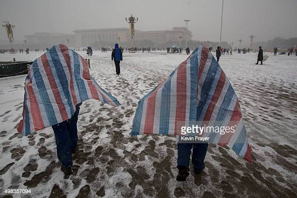 Chinese workers wear tarps as they walk through a snow covered Tiananmen Square during a snowfall on November 22 2014 in Beijing China China's...