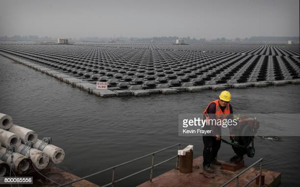 Chinese works on a large floating solar farm project under construction by the Sungrow Power Supply Company on a lake caused by a collapsed and...