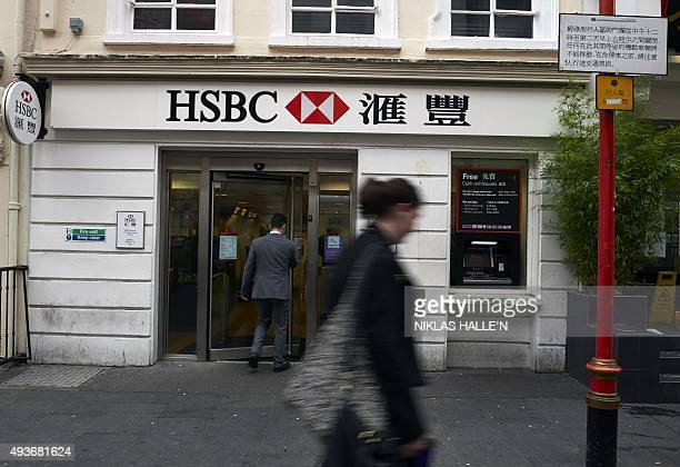 Chinese writing sits alonside a HSBC bank logo on a sign above the entrance a branch of the bank in London on October 22 2015 Britain's Competition...