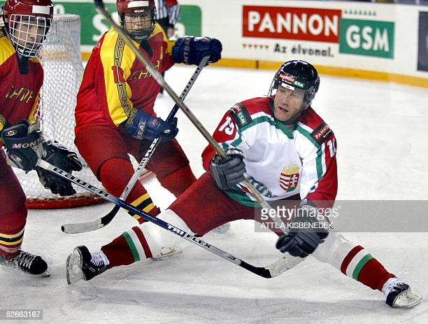 Chinese Yang Zhang and Siyan Qi and Hungarian forward Gabor Ocskay fight for the puck in the local 'Phonix' sports hall 20 April 2005 during their...