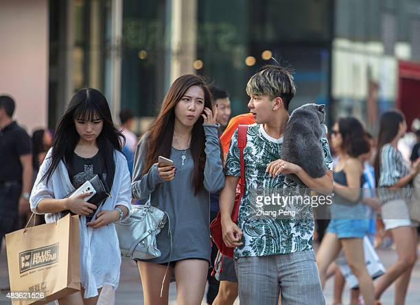 Chinese young boy carries his pet a pure breed British Shorthair cat on his shoulder strolling with his friends on the downtown street More and more...
