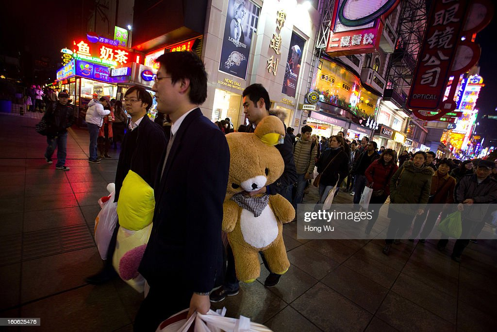 Chinese young people carry a cartoon bear toy in Nanjing Road Walking Street on February 3, 2013 in Shanghai, China.
