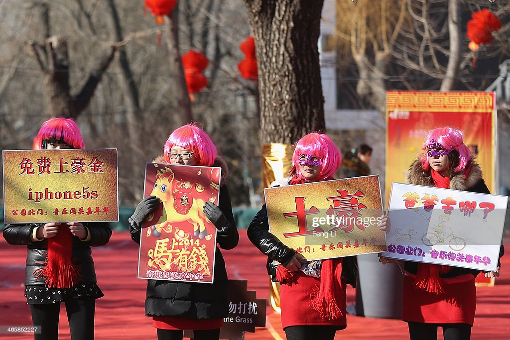 Chinese young women show brand to guide visitors at the Spring Festival Temple Fair for celebrating Chinese Lunar New Year of Horse at the Temple of Earth park on January 30, 2014 in Beijing, China. The Chinese Lunar New Year of Horse also known as the Spring Festival, which is based on the Lunisolar Chinese calendar, is celebrated from the first day of the first month of the lunar year and ends with Lantern Festival on the Fifteenth day.