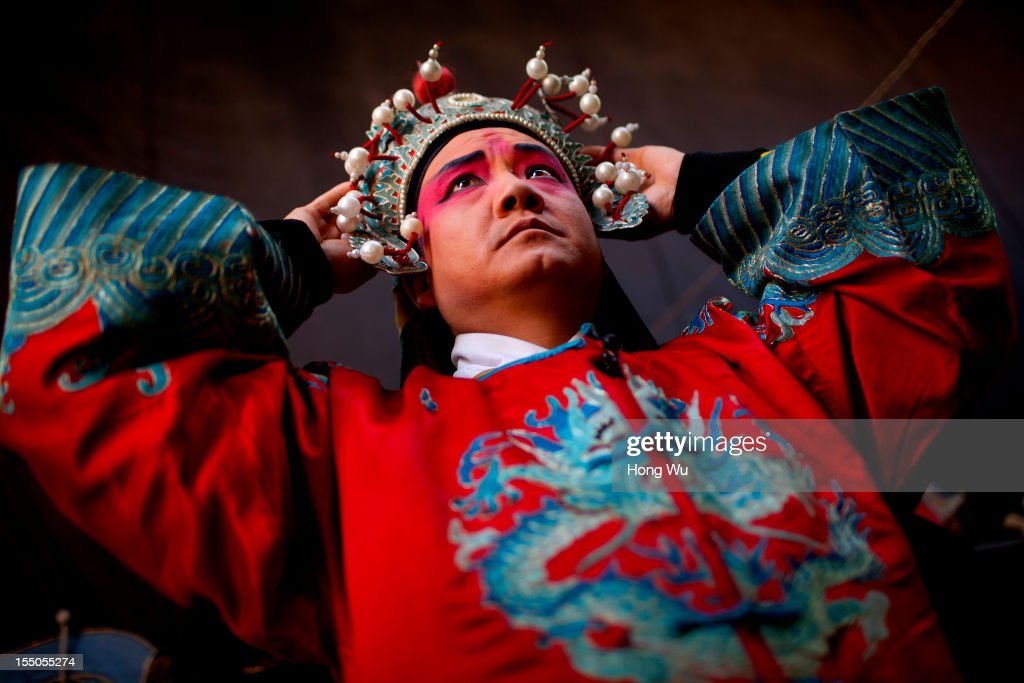 A Chinese Yu Opera performer, Li Yongli prepares backsateg on October 30, 2012 in Zhengzhou, China. As many as 60 performers from the Sanmenxia theatrical troupe are invited to perform Chinese traditional Yu Opera for local villagers in rural Zhengzhou city to celebrate the village's temple fair and earn 10,000 RMB yuan (US$ 1,600) each performance. Yu Opera, also called Henan Bangzi or Ou Opera, is one of the most popular local operas in China. Its earliest written record can be traced back more than 200 years and at the end of the Qing Dynasty (A.D. 1644-1911), the opera became widespread across the Henan province. After the establishment of the People's Republic of China in 1949, it experienced rapid growth not only in the villages and cities of Henan Province but also throughout the country. In recent years its popularity has declined due to young people's attraction to more modern cultures. (Photo by Hong Wu/Getty Image