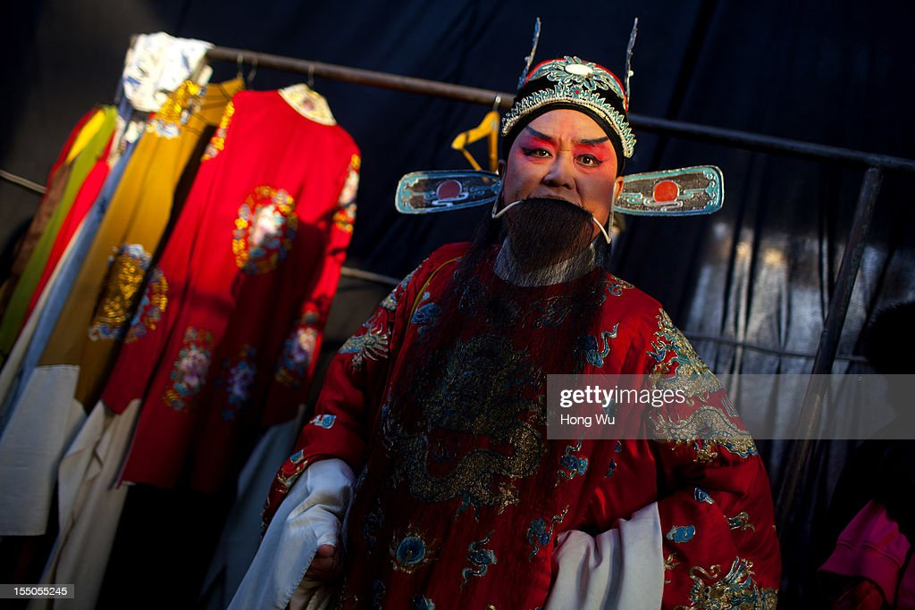 A Chinese Yu Opera performer, Li Yongli rehearses backstage on October 30, 2012 in Zhengzhou, China. As many as 60 performers from the Sanmenxia theatrical troupe are invited to perform Chinese traditional Yu Opera for local villagers in rural Zhengzhou city to celebrate the village's temple fair and earn 10,000 RMB yuan (US$ 1,600) each performance. Yu Opera, also called Henan Bangzi or Ou Opera, is one of the most popular local operas in China. Its earliest written record can be traced back more than 200 years and at the end of the Qing Dynasty (A.D. 1644-1911), the opera became widespread across the Henan province. After the establishment of the People's Republic of China in 1949, it experienced rapid growth not only in the villages and cities of Henan Province but also throughout the country. In recent years its popularity has declined due to young people's attraction to more modern cultures. (Photo by Hong Wu/Getty Images