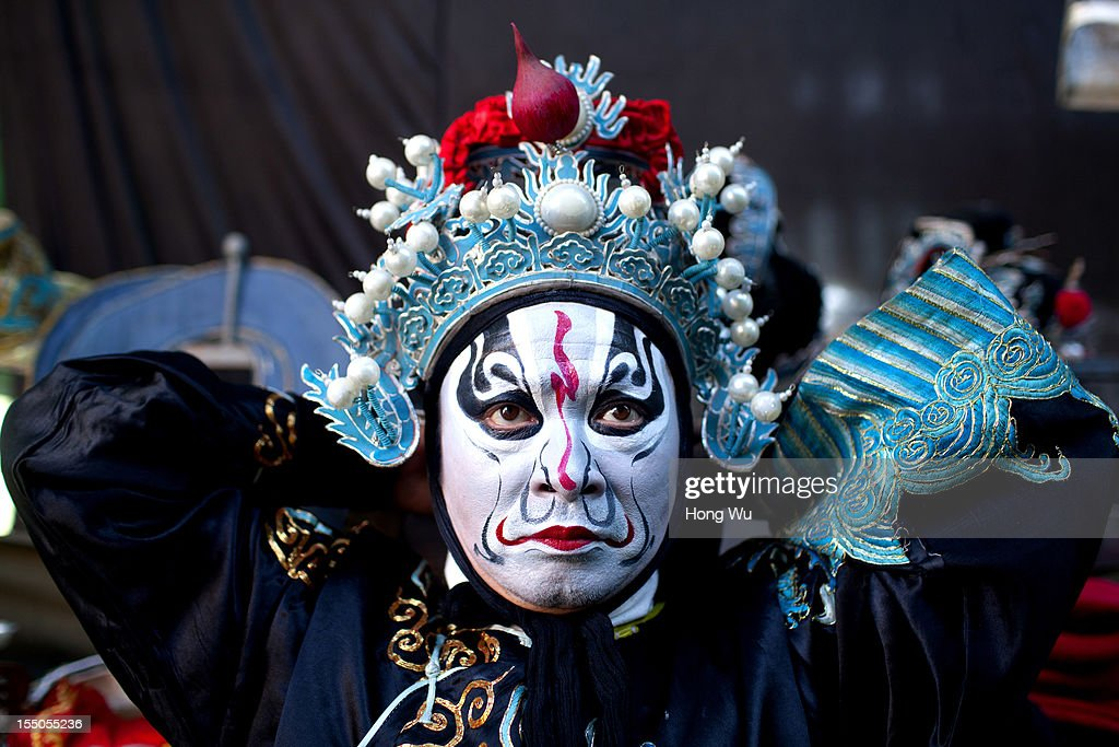 A Chinese Yu Opera performer prepares backstage ahead of the performance on October 30, 2012 in Zhengzhou, China. As many as 60 performers from the Sanmenxia theatrical troupe are invited to perform Chinese traditional Yu Opera for local villagers in rural Zhengzhou city to celebrate the village's temple fair and earn 10,000 RMB yuan (US$ 1,600) each performance. Yu Opera, also called Henan Bangzi or Ou Opera, is one of the most popular local operas in China. Its earliest written record can be traced back more than 200 years and at the end of the Qing Dynasty (A.D. 1644-1911), the opera became widespread across the Henan province. After the establishment of the People's Republic of China in 1949, it experienced rapid growth not only in the villages and cities of Henan Province but also throughout the country. In recent years its popularity has declined due to young people's attraction to more modern cultures.