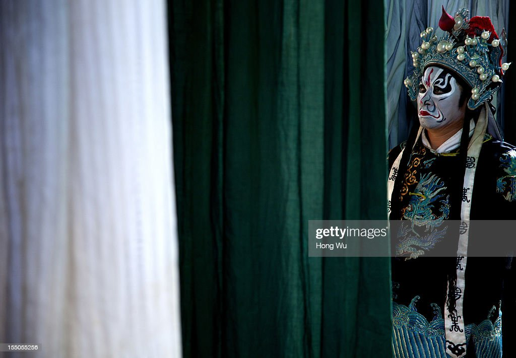 A Chinese Yu Opera performer waits backstage on October 30, 2012 in Zhengzhou, China. As many as 60 performers from the Sanmenxia theatrical troupe are invited to perform Chinese traditional Yu Opera for local villagers in rural Zhengzhou city to celebrate the village's temple fair and earn 10,000 RMB yuan (US$ 1,600) each performance. Yu Opera, also called Henan Bangzi or Ou Opera, is one of the most popular local operas in China. Its earliest written record can be traced back more than 200 years and at the end of the Qing Dynasty (A.D. 1644-1911), the opera became widespread across the Henan province. After the establishment of the People's Republic of China in 1949, it experienced rapid growth not only in the villages and cities of Henan Province but also throughout the country. In recent years its popularity has declined due to young people's attraction to more modern cultures.