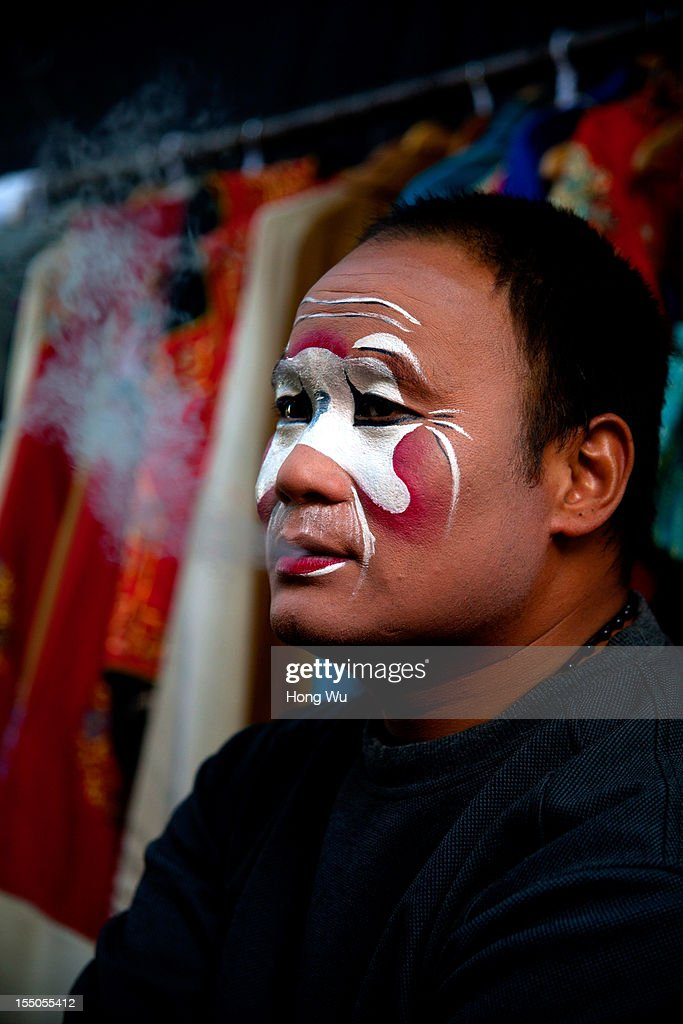 A Chinese Yu Opera performer waits to perform on October 30, 2012 in Zhengzhou, China. As many as 60 performers from the Sanmenxia theatrical troupe are invited to perform Chinese traditional Yu Opera for local villagers in rural Zhengzhou city to celebrate the village's temple fair and earn 10,000 RMB yuan (US$ 1,600) each performance. Yu Opera, also called Henan Bangzi or Ou Opera, is one of the most popular local operas in China. Its earliest written record can be traced back more than 200 years and at the end of the Qing Dynasty (A.D. 1644-1911), the opera became widespread across the Henan province. After the establishment of the People's Republic of China in 1949, it experienced rapid growth not only in the villages and cities of Henan Province but also throughout the country. In recent years its popularity has declined due to young people's attraction to more modern cultures.