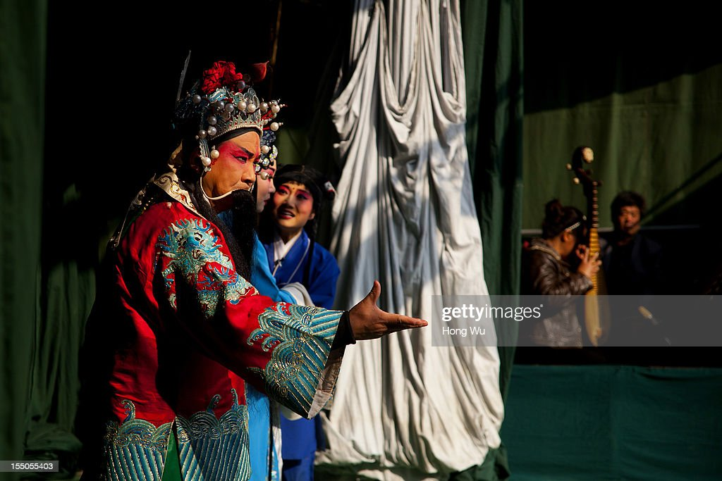 Chinese Yu Opera performers perform onstage on October 30, 2012 in Zhengzhou, China. As many as 60 performers from the Sanmenxia theatrical troupe are invited to perform Chinese traditional Yu Opera for local villagers in rural Zhengzhou city to celebrate the village's temple fair and earn 10,000 RMB yuan (US$ 1,600) each performance. Yu Opera, also called Henan Bangzi or Ou Opera, is one of the most popular local operas in China. Its earliest written record can be traced back more than 200 years and at the end of the Qing Dynasty (A.D. 1644-1911), the opera became widespread across the Henan province. After the establishment of the People's Republic of China in 1949, it experienced rapid growth not only in the villages and cities of Henan Province but also throughout the country. In recent years its popularity has declined due to young people's attraction to more modern cultures.