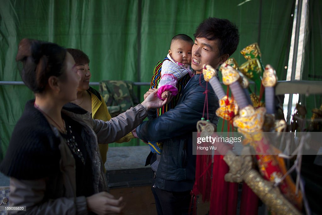 Chinese Yu Opera performers play with a baby backstage on October 30, 2012 in Zhengzhou, China. As many as 60 performers from the Sanmenxia theatrical troupe are invited to perform Chinese traditional Yu Opera for local villagers in rural Zhengzhou city to celebrate the village's temple fair and earn 10,000 RMB yuan (US$ 1,600) each performance. Yu Opera, also called Henan Bangzi or Ou Opera, is one of the most popular local operas in China. Its earliest written record can be traced back more than 200 years and at the end of the Qing Dynasty (A.D. 1644-1911), the opera became widespread across the Henan province. After the establishment of the People's Republic of China in 1949, it experienced rapid growth not only in the villages and cities of Henan Province but also throughout the country. In recent years its popularity has declined due to young people's attraction to more modern cultures.