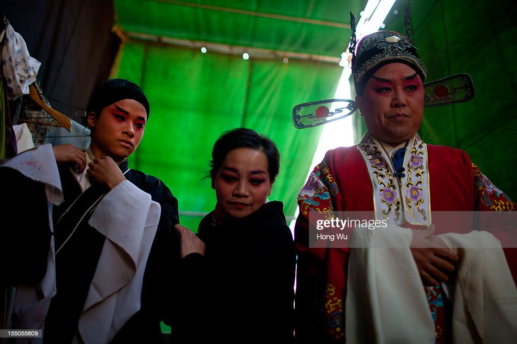 Chinese Yu Opera performers prepare backstage on October 30, 2012 in Zhengzhou, China. As many as 60 performers from the Sanmenxia theatrical troupe are invited to perform Chinese traditional Yu Opera for local villagers in rural Zhengzhou city to celebrate the village's temple fair and earn 10,000 RMB yuan (US$ 1,600) each performance. Yu Opera, also called Henan Bangzi or Ou Opera, is one of the most popular local operas in China. Its earliest written record can be traced back more than 200 years and at the end of the Qing Dynasty (A.D. 1644-1911), the opera became widespread across the Henan province. After the establishment of the People's Republic of China in 1949, it experienced rapid growth not only in the villages and cities of Henan Province but also throughout the country. In recent years its popularity has declined due to young people's attraction to more modern cultures.