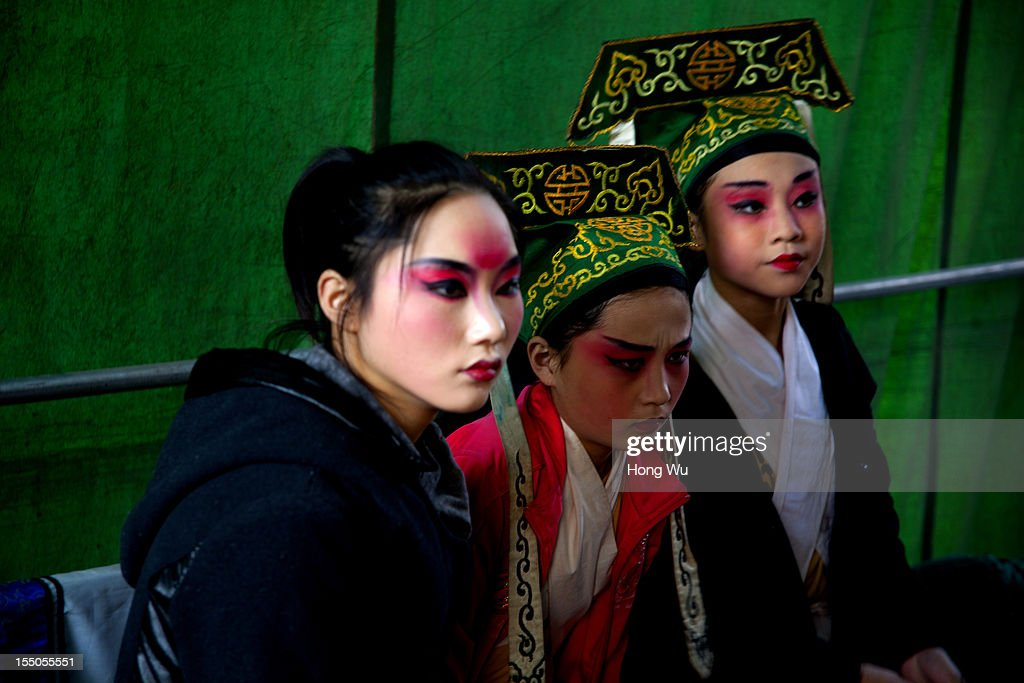 Chinese Yu Opera performers wait to perform backstage on October 30, 2012 in Zhengzhou, China. As many as 60 performers from the Sanmenxia theatrical troupe are invited to perform Chinese traditional Yu Opera for local villagers in rural Zhengzhou city to celebrate the village's temple fair and earn 10,000 RMB yuan (US$ 1,600) each performance. Yu Opera, also called Henan Bangzi or Ou Opera, is one of the most popular local operas in China. Its earliest written record can be traced back more than 200 years and at the end of the Qing Dynasty (A.D. 1644-1911), the opera became widespread across the Henan province. After the establishment of the People's Republic of China in 1949, it experienced rapid growth not only in the villages and cities of Henan Province but also throughout the country. In recent years its popularity has declined due to young people's attraction to more modern cultures.