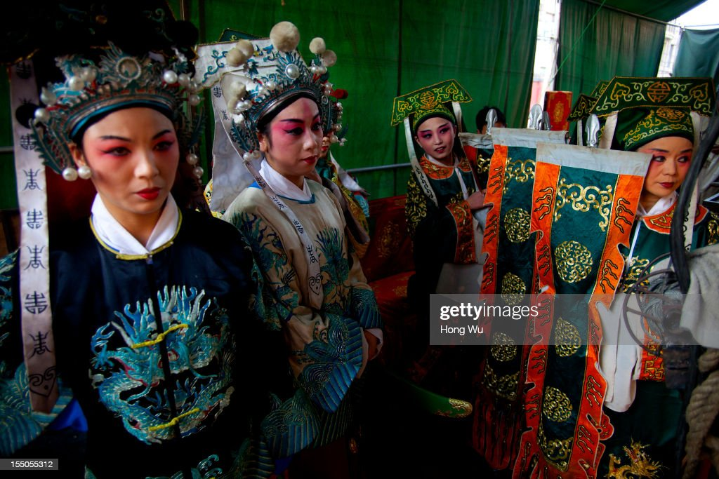 Chinese Yu Opera performers wait to perform on October 30, 2012 in Zhengzhou, China. As many as 60 performers from the Sanmenxia theatrical troupe are invited to perform Chinese traditional Yu Opera for local villagers in rural Zhengzhou city to celebrate the village's temple fair and earn 10,000 RMB yuan (US$ 1,600) each performance. Yu Opera, also called Henan Bangzi or Ou Opera, is one of the most popular local operas in China. Its earliest written record can be traced back more than 200 years and at the end of the Qing Dynasty (A.D. 1644-1911), the opera became widespread across the Henan province. After the establishment of the People's Republic of China in 1949, it experienced rapid growth not only in the villages and cities of Henan Province but also throughout the country. In recent years its popularity has declined due to young people's attraction to more modern cultures.
