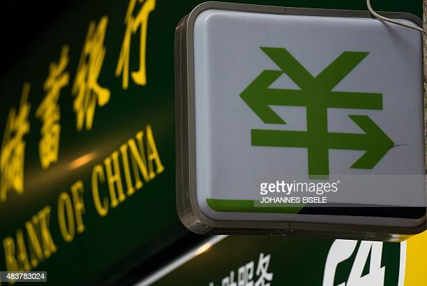 A Chinese yuan currency sign with two arrows is pictured outside a bank branch in Shanghai on August 13 2015 China cut the reference rate for its...