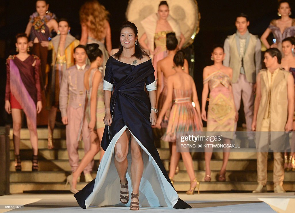 Chiness tennis star Li Na (C) walks the cat walk during the Thai silk fashion show in Thailand's resort seaside town of Hua Hin on December 28, 2012. Azarenka will play an exhibition match with Li Na at the Hua Hin World Tennis Invitation on December 29. AFP PHOTO / PORNCHAI KITTIWONGSAKUL