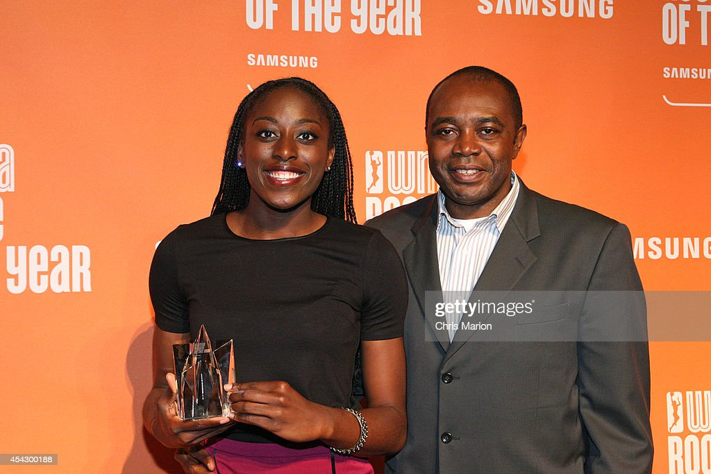 Chiney Ogwumike of the Connecticut Sun poses with her father and the 2014 WNBA Rookie Of The Year Award at a press conference on August 28, 2014 at the Mohegan Sun Casino in Uncasville, Connecticut.