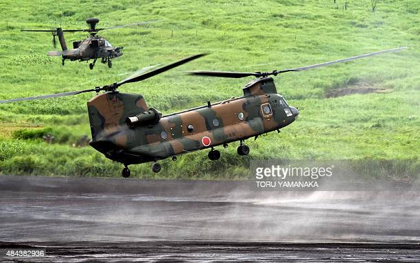 Chinook heavy lift helicopter escorted by an AH64DJP Apache attack helicopter prepares to land Japanese Ground SelfDefense Force troops during an...