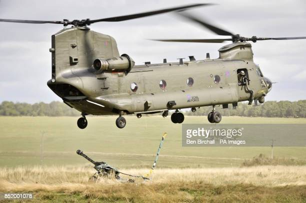A Chinook helicopter drops a 105 Gun on the Wiltshire military training ground of Salisbury Plain as 7th Armoured Brigade prepare to deploy to...