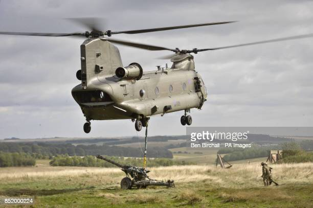 A Chinook helicopter flies low and lifts a 105 Gun on the Wiltshire military training ground of Salisbury Plain as 7th Armoured Brigade prepare to...