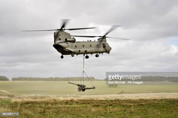 A Chinook helicopter lifts a 105 Gun on the Wiltshire military training ground of Salisbury Plain as 7th Armoured Brigade prepare to deploy to...