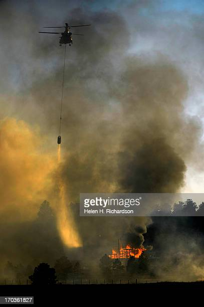 A chinook helicopter makes a water drop on a burning structure in the midst of the Black Forest Fire in Colorado Springs CO on June 11 2013 Many...