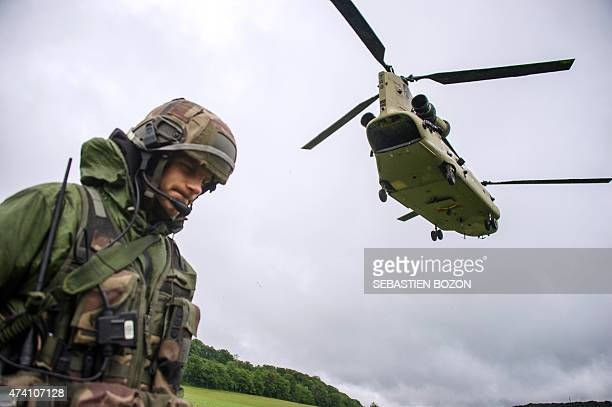 Chinook helicopter passes over a French soldier during a FrenchUS 'Royal Blackhawk' military exercise with French US Dutch British and Belgian troops...