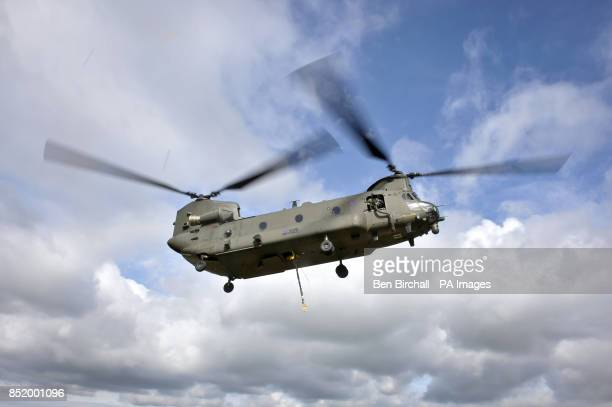 A Chinook helicopter prepares to lift a 105 Gun on the Wiltshire military training ground of Salisbury Plain as 7th Armoured Brigade prepare to...