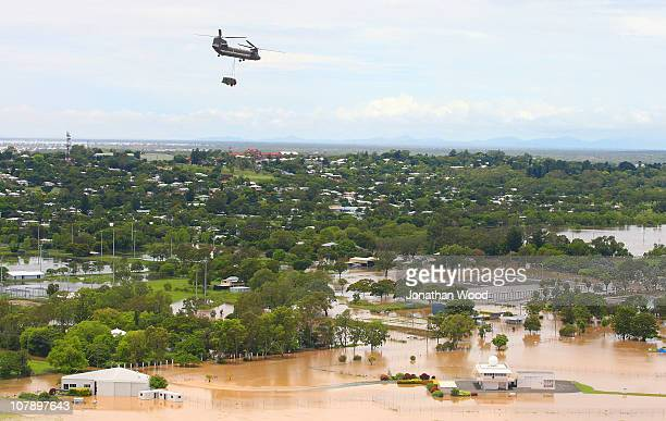 A chinook helicopter with supplied flies over houses affected by flood waters on January 6 2011 in Rockhampton Australia Floodwaters peaked at 92...