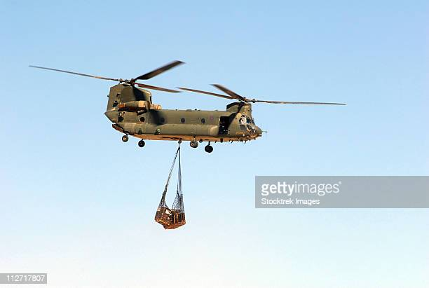 A CH-47 Chinook of the Royal Air Force transports a sling load of pallets.