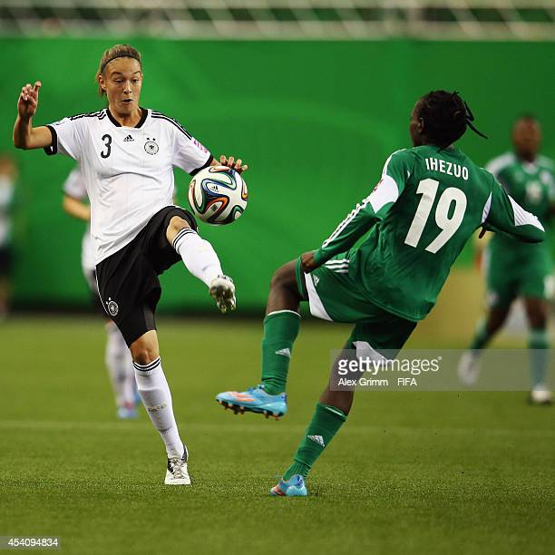 Chinwendu Ihezuo of Nigeria is challenged by Felicitas Rauch of Germany during the FIFA U20 Women's World Cup Canada 2014 final match between Nigeria...
