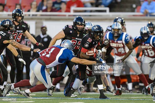 Chip Cox of the Montreal Alouettes tackles Marcus Henry of the Ottawa Redblacks during the CFL game at Percival Molson Stadium on August 29 2014 in...