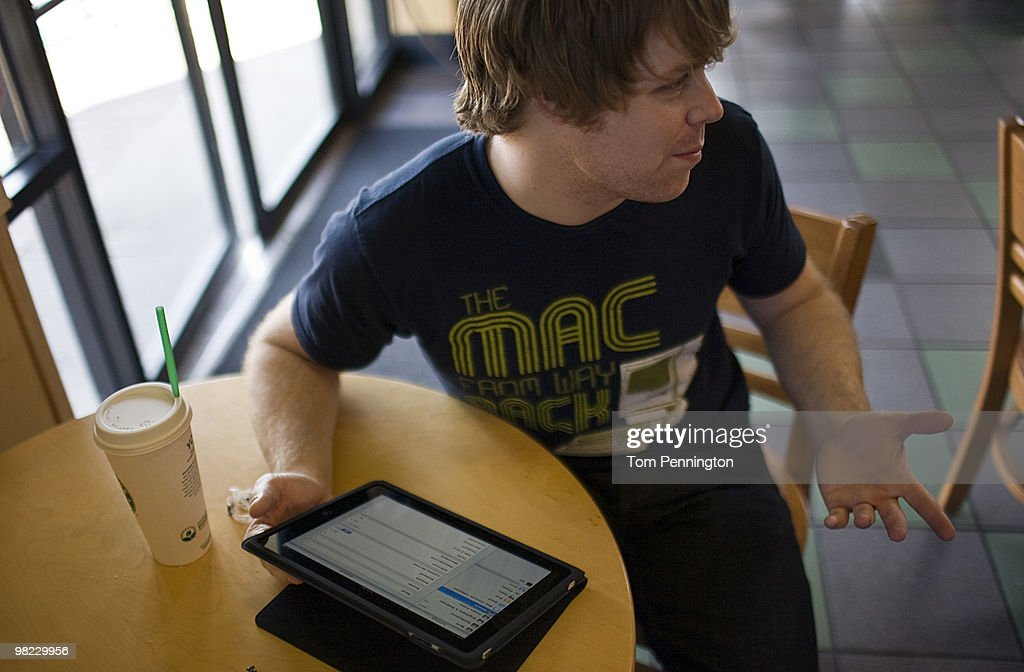 Chip Hanna, 26, describes his newly purchased iPad to other customers while visiting a Starbucks Coffee location April 3, 2010 in Fort Worth, Texas. Debuting today, the much heralded iPad looks to be a bridge between a laptop and smartphone.