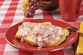 A plate of creamed chipped beef on toast with a drink