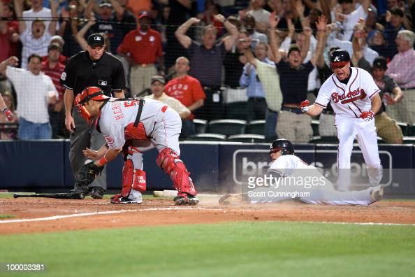 Chipper Jones of the Atlanta Braves celebrates after Martin Prado scores the gamewinning run against Ramon Hernandez of the Cincinnati Reds at Turner...