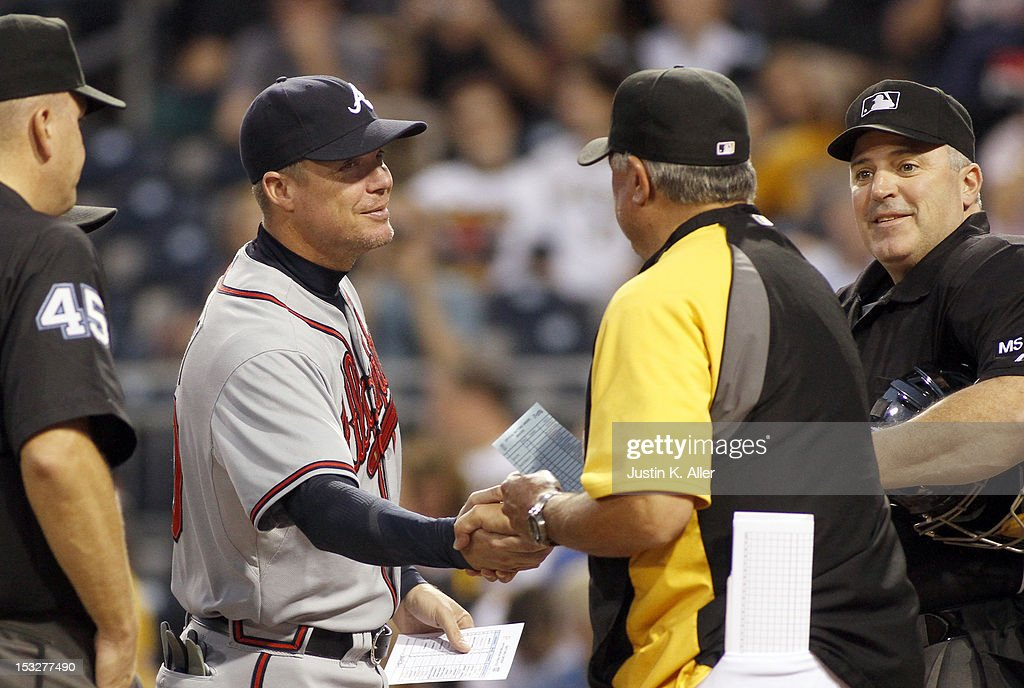 Chipper Jones #10 of the Atlanta Braves exchanges score cards with manager Clint Hurdle #13 of the Pittsburgh Pirates during the game on October 2, 2012 at PNC Park in Pittsburgh, Pennsylvania.