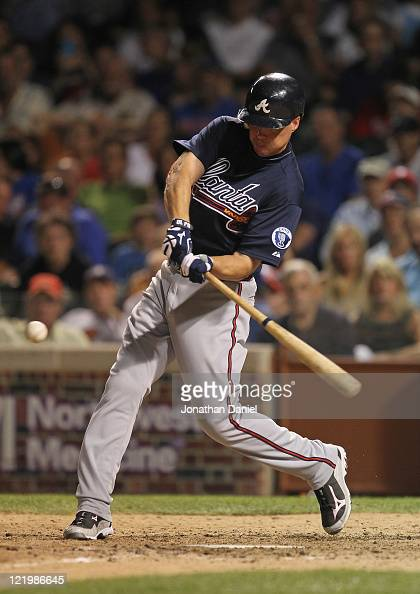 Chipper Jones of the Atlanta Braves hits his 13th home run of the year a solo shot in the 7th inning against the Chicago Cubs at Wrigley Field on...