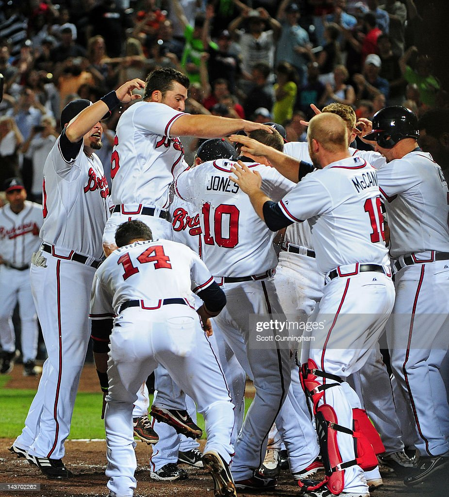 <a gi-track='captionPersonalityLinkClicked' href=/galleries/search?phrase=Chipper+Jones&family=editorial&specificpeople=171256 ng-click='$event.stopPropagation()'>Chipper Jones</a> #10 of the Atlanta Braves is congratulated by teammates after hitting a 11th inning walk off home run against the Philadelphia Phillies at Turner Field on May 2, 2012 in Atlanta, Georgia.