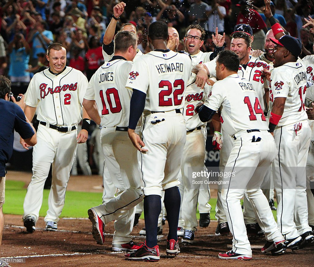 <a gi-track='captionPersonalityLinkClicked' href=/galleries/search?phrase=Chipper+Jones&family=editorial&specificpeople=171256 ng-click='$event.stopPropagation()'>Chipper Jones</a> #10 of the Atlanta Braves is mobbed by teammates after hitting a three-run walk-off home run against the Philadelphia Phillies at Turner Field on September 2 2012 in Atlanta, Georgia.