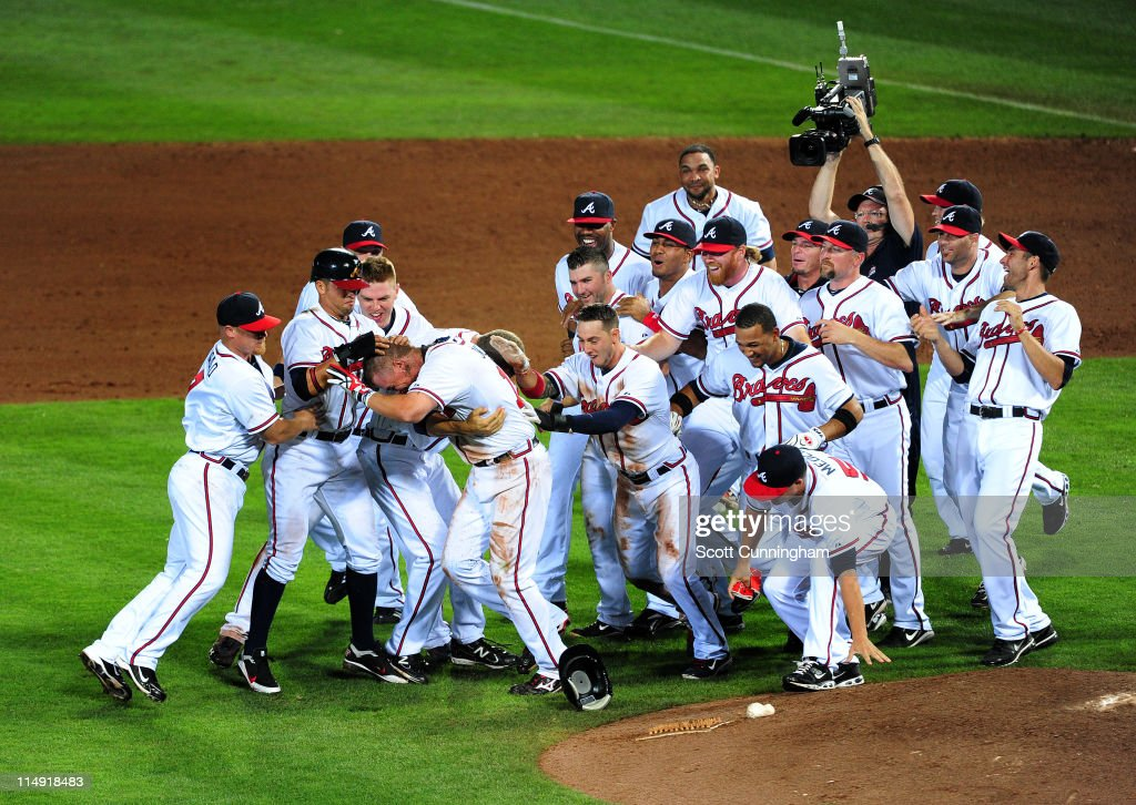 Chipper Jones of the Atlanta Braves is mobbed by teammates after knocking in the winning run in the 12th inning against the Cincinnati Reds at Turner...